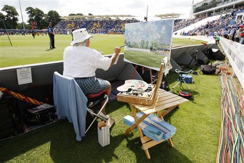 Artist Jocelyn Galsworthy works on a painting on the third day of the first Test match between England and Australia in Cardiff, Wales. (AP Photo)