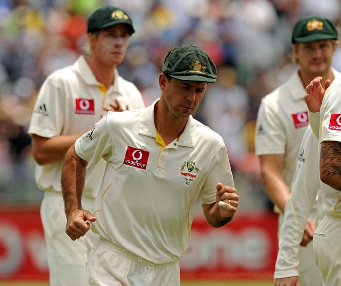 Australian captain Ricky Ponting (with his injured finger showing) runs from the ground with teammates after they defeated England on day four of the third Ashes cricket Test at the WACA Ground in Perth. (AFP Photo)