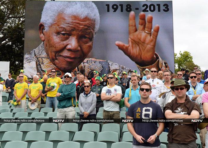 The Australia and England cricket teams paid tribute to Nelson Mandela at Adelaide on Friday, wearing black armbands and observing a minute's silence. Both teams lined up in Mandela's honour ahead of the second day's play at Adelaide Oval as a photo of the anti-apartheid hero was shown on the ground's large video screen. (All AFP images)