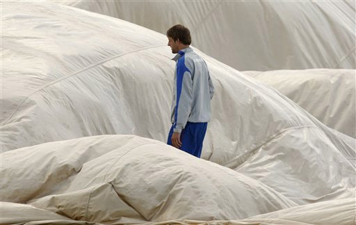 A member of the groundstaff helps to move a protective cover as rain delays play on the first day of the third Test between England and Australia in Birmingham. (AP Photo)