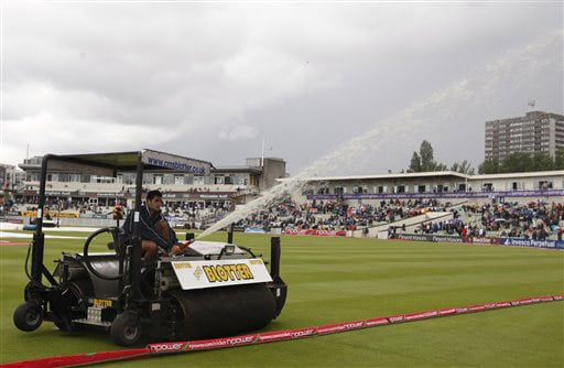 Water is drained from the pitch by a 'blotter' machine, as rain delays the start of play on the first day of the third Ashes Test between England and Australia in Birmingham. (AP Photo)