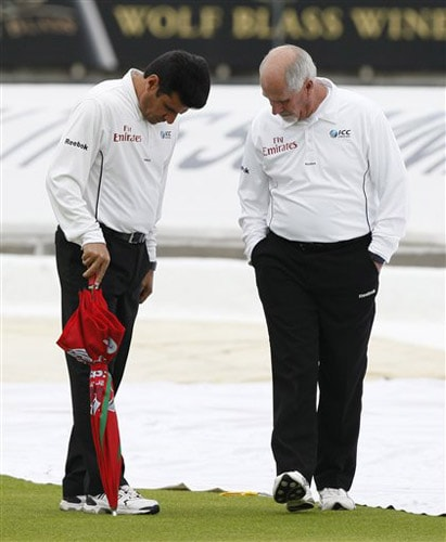 Umpires Aleem Dar and Rudi Koertzen perform a pitch inspection on a rain affected third day of the third Test between England and Australia in Birmingham. (AP Photo)