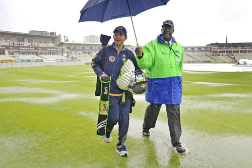 Australian captain Ricky Ponting walks through the flooded outfield as play is abandoned on Day 3 of the third Ashes Test between England and Australia at Edgbaston. (AFP Photo)