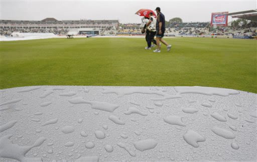 Rain drops are seen on a pitch side drinks container as Australian team members pass by, rain delayed play on the third day of the third Test between England and Australia at Edgbaston. (AP Photo)