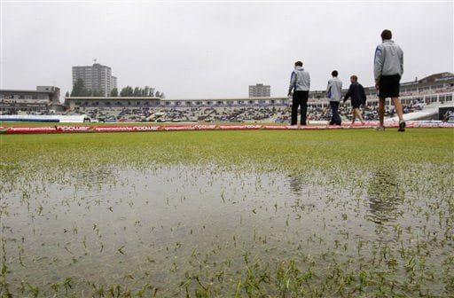 Groundsmen walk past a puddle on the outfield as rain delays play on the third day of the third Test between England and Australia at Edgbaston. (AP Photo)