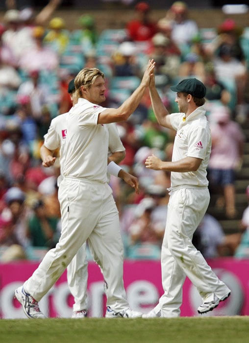 Australia's bowler Shane Watson is congratulated by teammate Phil Hughes after England batsman Alastair Cook was caught out during the third day of the fifth Ashes Test at the Sydney Cricket Ground (SCG) in Sydney. (AFP Photo)
