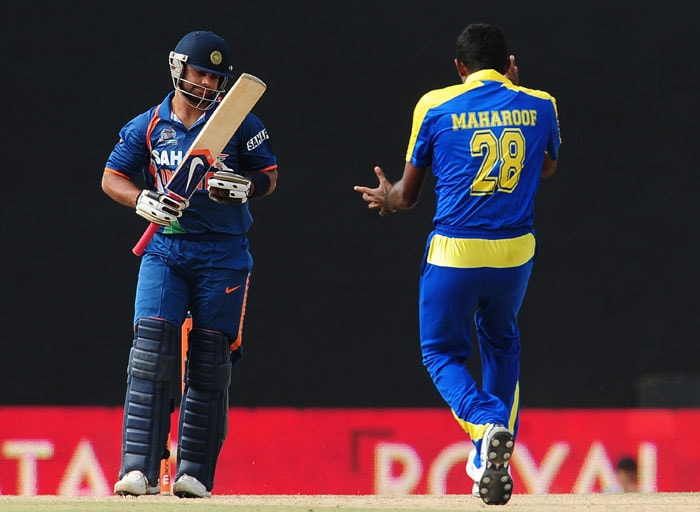 Farveez Maharoof celebrates the dismissal of Indian cricketer Virat Kohli (L) during the sixth ODI of the Asia Cup between Sri Lanka and Indian at the Rangiri Dambulla International Cricket stadium in Dambulla. (AFP Photo)