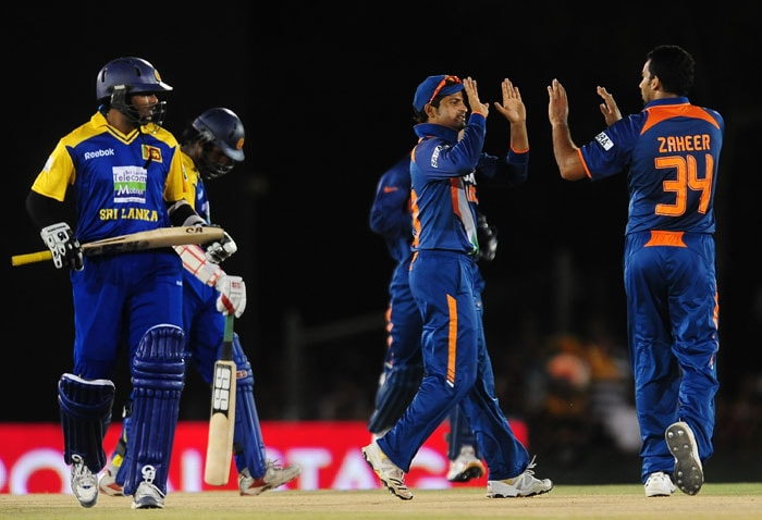Zaheer Khan celebrates with his teammate Suresh Raina after he dismissed Tillakaratne Dilshan during the sixth ODI of the Asia Cup between Sri Lanka and Indian at the Rangiri Dambulla International stadium in Dambulla. (AFP Photo)