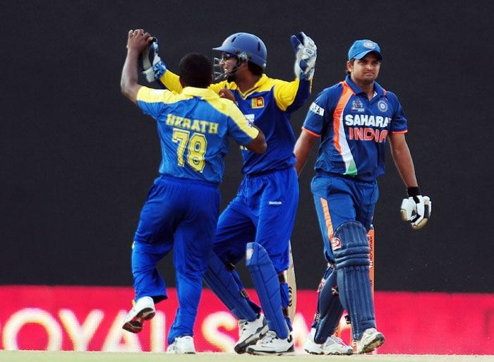 Rangana Herath and captian Kumar Sangakkara celebrate after dismissing Suresh Raina during the sixth ODI of the Asia Cup between Sri Lanka and Indian at the Rangiri Dambulla International Cricket stadium in Dambulla. (AFP Photo)