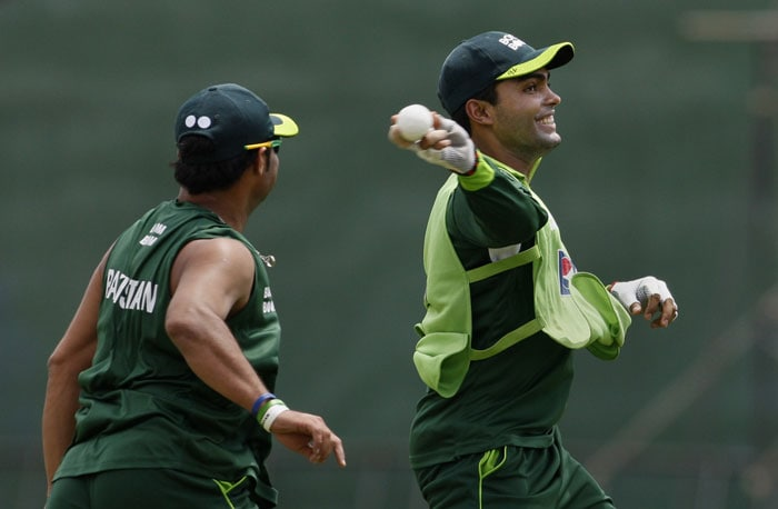 Pakistan player Umar Akmal runs with a ball as teammate Fawad Allam follows during a practice session ahead of the Asia Cup match against Sri Lanka in Dambulla. (AP Photo)