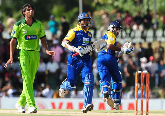 Mohammad Asif watches on as Kumar Sangakkara and teammate Mahela Jayawardene run between the wickets during the first ODI of the Asia Cup. (AFP Photo)