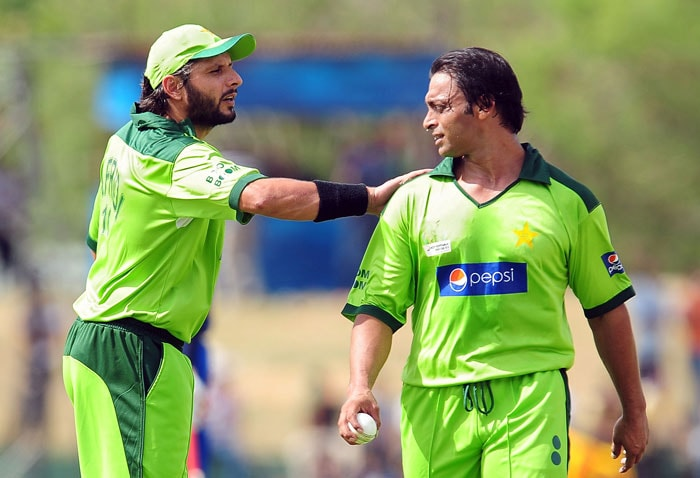 Shahid Afridi speaks with teammate Shoaib Akhtar during the first ODI of the Asia Cup. (AFP Photo)