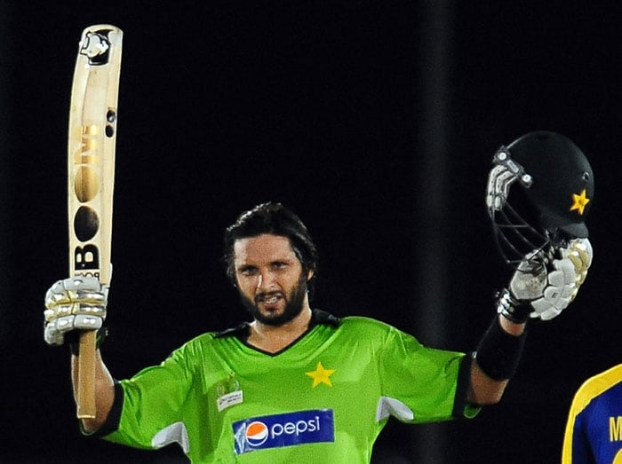 Pakistan captain Shahid Afridi raises his bat and helmet in celebration after scoring a century during the first ODI of the Asia Cup. (AFP Photo)