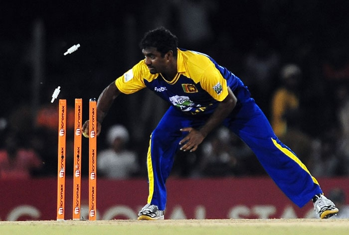 Muttiah Muralitharan breaks the wicket as he runs out Kamran Akmal during the first ODI of the Asia Cup. (AFP Photo)