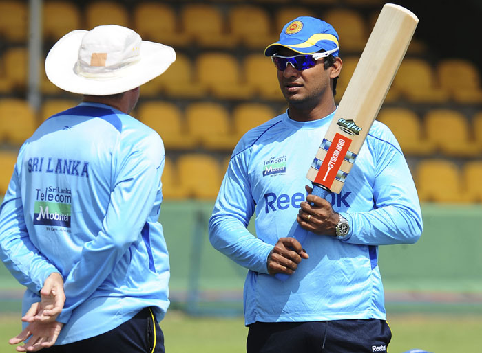 Sri Lankan captain Kumar Sangakkara speaks with team coach Trevor Bayliss during a team practice session at the Rangiri Dambulla International stadium in Dambulla, some 150 kms north of Colombo. Asia's Test-playing nations begin their preparations for next year's World Cup when they contest the region's top one-day prize. (AFP Photo)