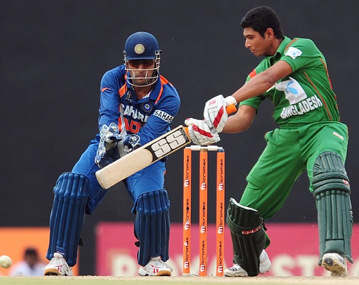 Bangladeshi cricketer Mahmudullah plays a shot as Indian wicketkeeper and captain Mahendra Singh Dhoni reacts during the second ODI of the Asia Cup, played at the Rangiri Dambulla International Cricket stadium in Dambulla. (AFP Photo)