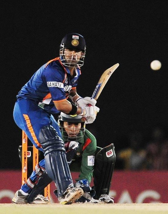 Indian cricketer Gautam Gambhir plays a shot while Bangladeshi wicketkeeper Mushfiqur Rahim looks on during the second ODI of the Asia Cup, played at the Rangiri Dambulla International Cricket stadium in Dambulla. (AFP Photo)
