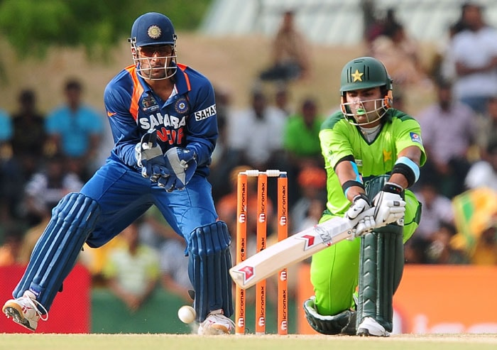 Umar Akmal plays a stroke as Mahendra Singh Dhoni watches on during the fourth ODI of the Asia Cup between India and Pakistan at the Rangiri Dambulla International Cricket stadium in Dambulla. (AFP Photo)