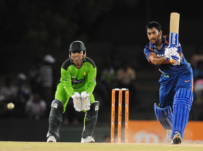Indian cricket captian Mahendra Singh Dhoni plays a stroke as Pakistan wicketkeeper Kamran Akmal watches on during the fourth ODI of the Asia Cup between India and Pakistan at the Rangiri Dambulla International Cricket stadium in Dambulla. (AFP Photo)