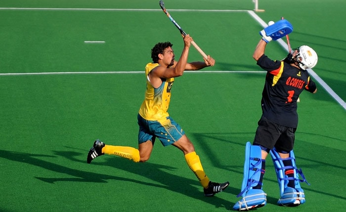 Australian hockey player Desmond Abbott vies for the ball with Spanish hockey goalkeeper Francisco Cortes (R) during their World Cup 2010 match at the Major Dhyan Chand Stadium in New Delhi. (AFP Photo)