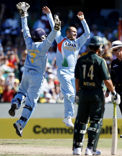 Virender Sehwag celebrates with his captain Mahendra Singh Dhoni, left, after running out Matthew Hayden during their one-day international at the Sydney Cricket Ground on Sunday, February 24, 2008.