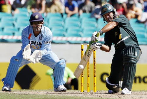 Ricky Ponting hits the ball as Mahendra Singh Dhoni, left, looks on during their one-day cricket international at the Sydney Cricket Ground on Sunday, February 24, 2008.