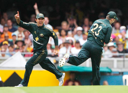 Australian captain Ricky Ponting left, celebrates as team-mate Michael Clarke right, takes a catch to dismiss Robin Uthappa during their One-Day cricket international in Brisbane on Sunday, February 03, 2008.