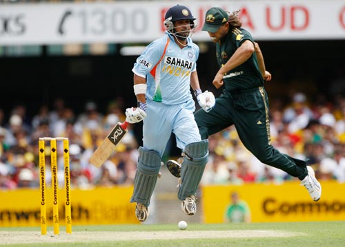 Gautam Gambhir runs to make his ground as Australian fieldsman Andrew Symonds right, attempts to kick the ball onto the stumps during their One-Day cricket international against Australia in Brisbane on Sunday, February 03, 2008