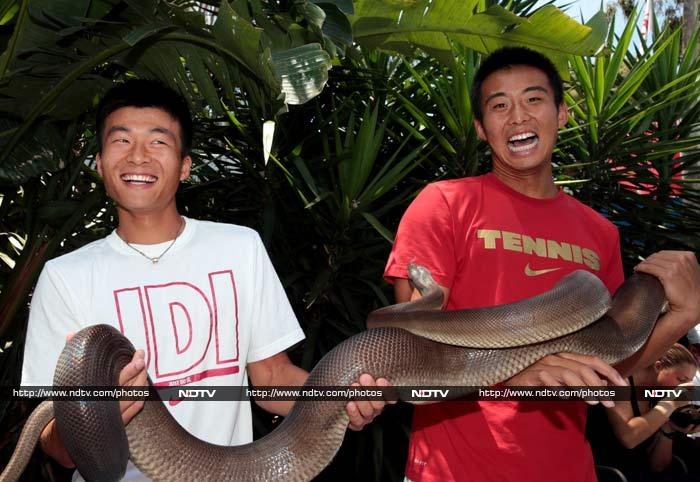 China's Wu Di and Zhang Ze are seen here holding the python. <br><br> The pyhton must clearly have had a lifetime's worth of snaps taken!