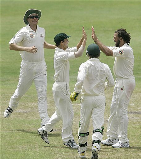 Australia's Beau Casson high fives with teammate Andrew Symonds as wicketkeeper Brad Haddin and Stuart Clark looks on, after Casson caught out West Indies batsman Xavier Marshall for 39 runs on the on the second day of their third and final Test at Kensington Oval in Bridgetown, Barbados on June 13, 2008.