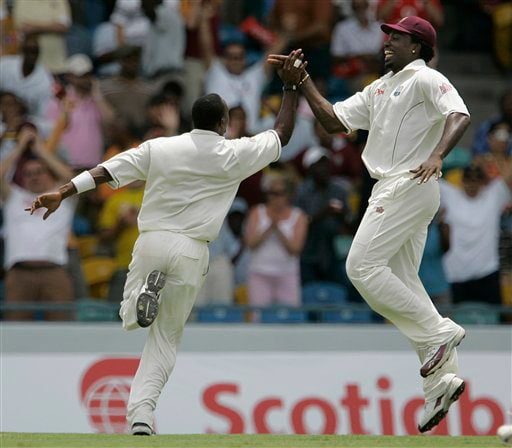 West Indies' captain Chris Gayle, right, highs five with teammate Dwayne Bravo celebrating the dismissal of Australia's Michael Clarke, who was caught behind for a duck, on the opening day of their third and final cricket Test match in Bridgetown on Thursday, June 12, 2008.