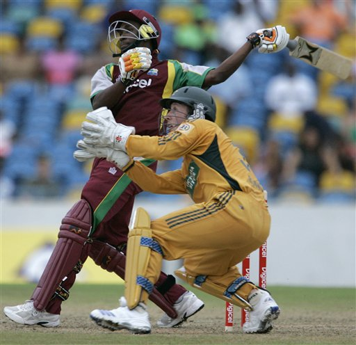 West Indies' batsman Dwayne Bravo, rear, hits a six off Australia's bowler Cameron White, unseen, as Australia's wicketkeeper Luke Ronchi looks on during their international Twenty20 cricket match at Kensington Oval in Bridgetown on Friday, June 20, 2008. The West Indies won by seven wickets in the 11-overs-per-side reduced match due to rain.