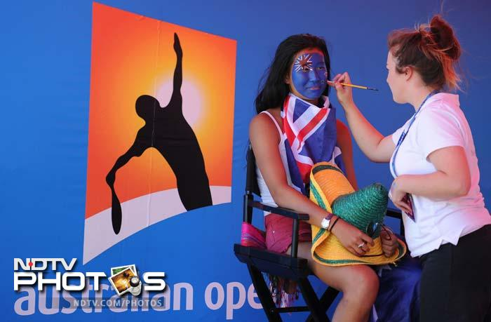 Of course, one does not need to be rich to earn the support from fans. One of them is seen here getting herself painted with the Australian flag.