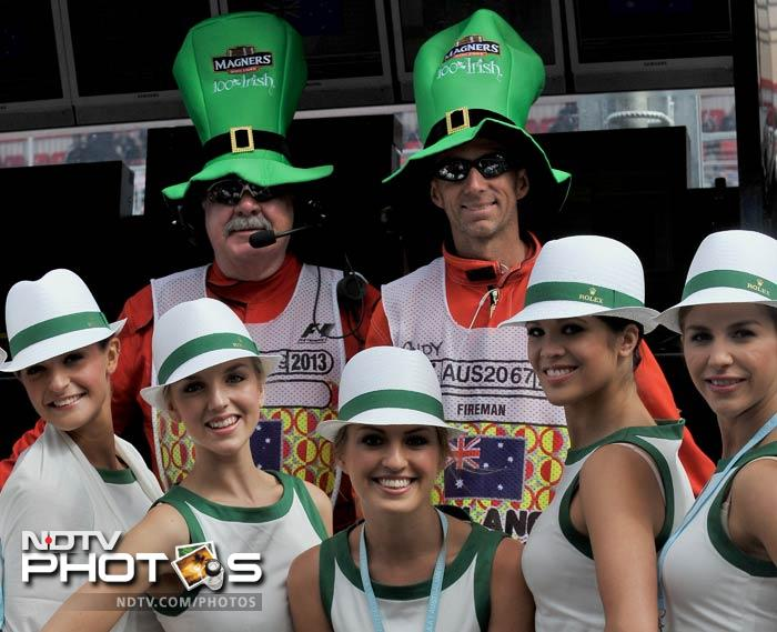 Pit lane fire marshalls get into the spirit of St Patrick's day with romotional girls ahead of the Formula One Australian Grand Prix in Melbourne on March 17, 2013. Sebastian Vettel of Germany started the first race of the season from pole position.