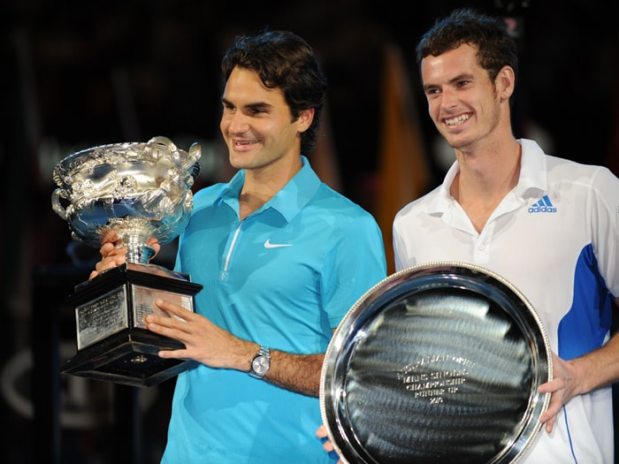Swiss Roger Federer (L) poses holding the winners trophy with British opponent Andy Murray holding the runners-up plate at the post match ceremony of the Australian Open men's singles final in Melbourne. (AFP Photo)