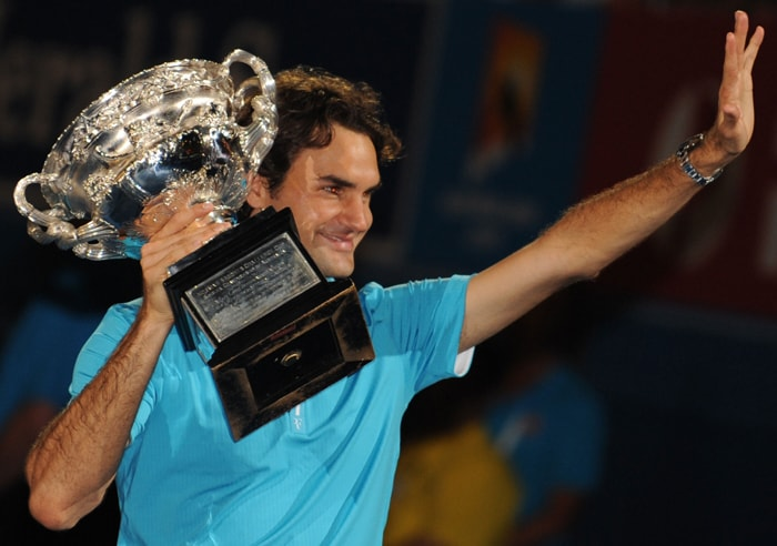 Roger Federer waves to the crowd holding the winners trophy after victory in his men's singles final match against British opponent Andy Murray at the Australian Open. (AFP Photo)