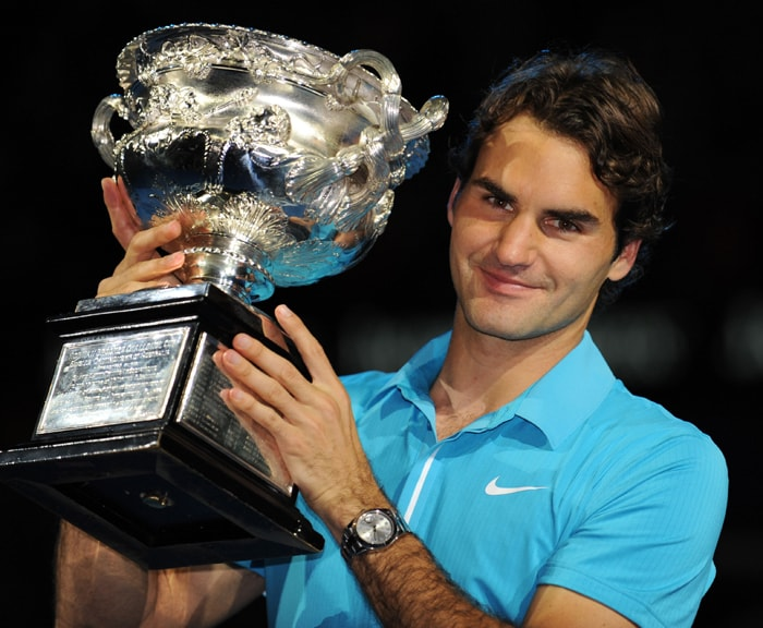 Roger Federer poses with the winners trophy after victory in his men's singles final match against British opponent Andy Murray at the Australian Open. Federer won 6-3, 6-4, 7-6 (13-11). (AFP Photo)