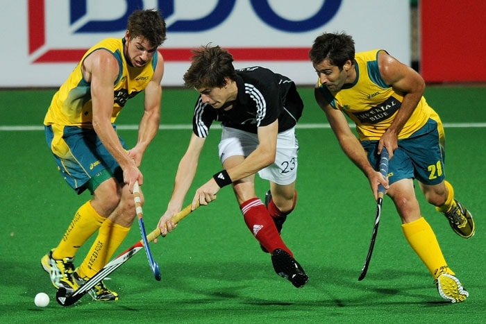 Australian Hockey player Kiel Brown (R) vies for the ball with German hockey player Florian Fuchs (C) during their World Cup 2010 Final match at the Major Dhyan Chand Stadium. (AFP Photo)