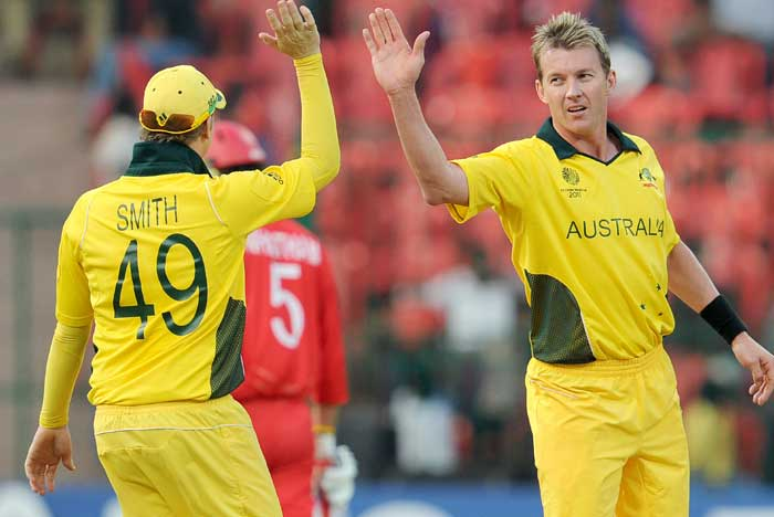 Australian fast bowler Brett Lee is congratulated by teammate Steve Smith after taking one of his four Canadian wickets. (AFP Photo)