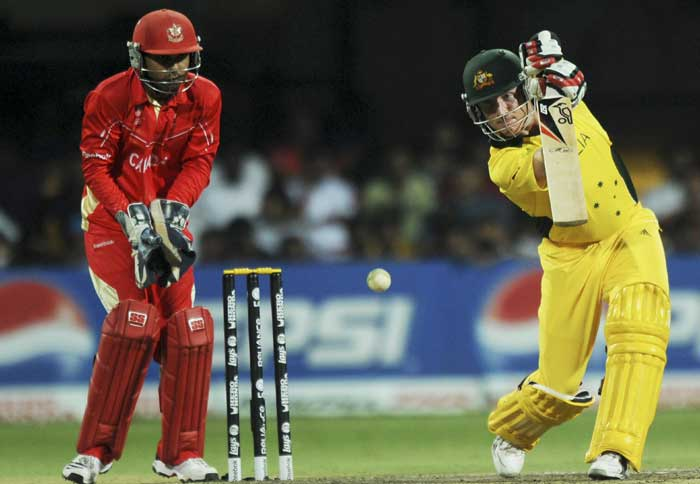 Australian batsman Brad Haddin watched by Canadian wicketkeeper Ashish Bagai plays a shot. (AFP Photo)