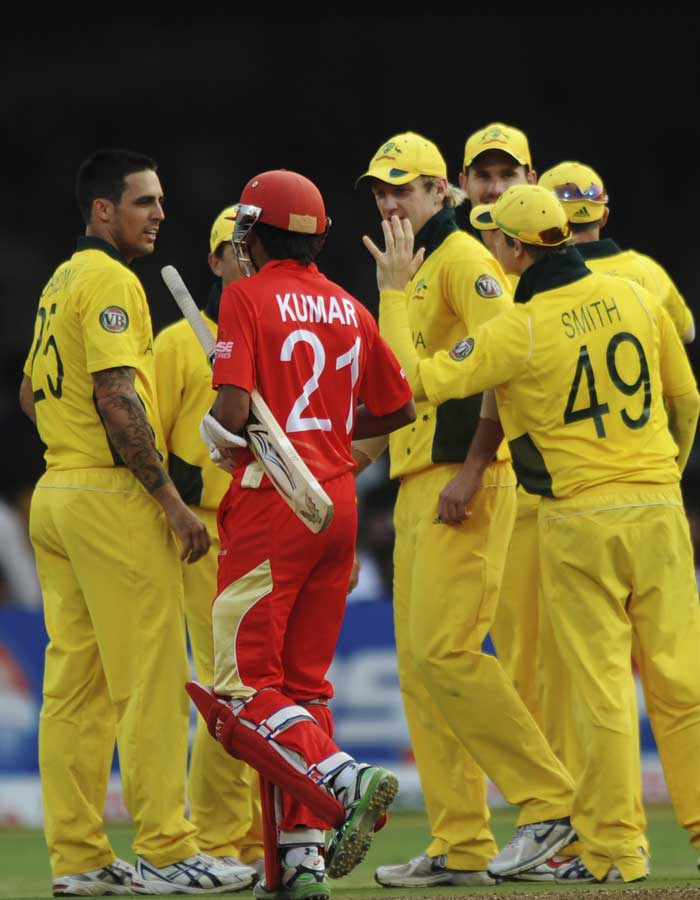 Australian players congratulate fast bowler Mitchell Johnson (L) after he took the wicket of Canadian batsman Nitish Kumar. (AFP Photo)