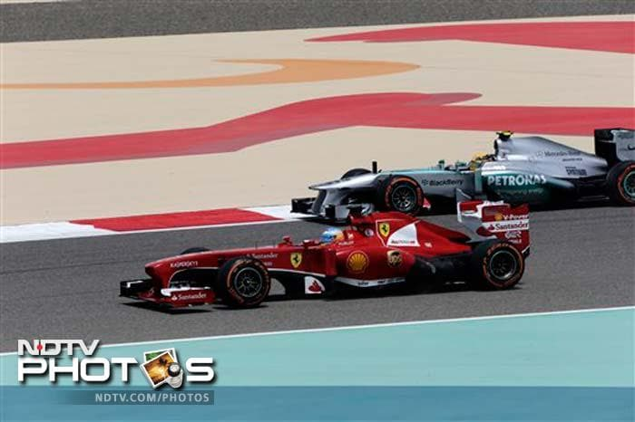Ferrari's Fernando Alonso and Mercedes' Lewis Hamilton steer their cars during first practice for the Bahrain Grand Prix.