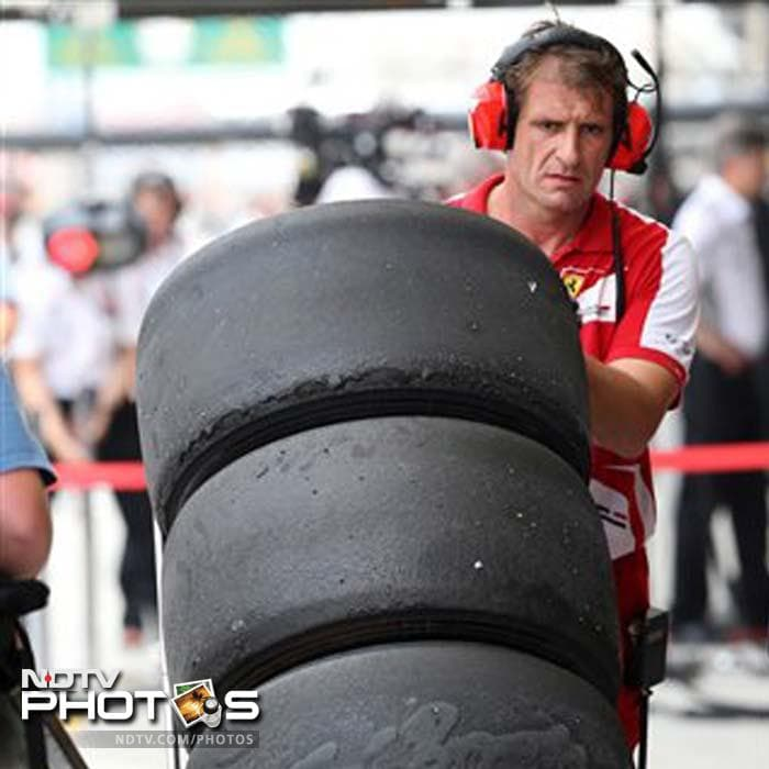 A Ferrari mechanic carries the used tires after the first practice session for the Bahrain Grand Prix at the Bahrain International Circuit in Sakhir.