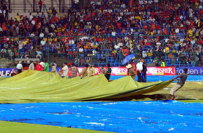The groundsmen had a tough time on the field getting the covers on and off. (AFP PHOTO/Manjunath KIRAN)