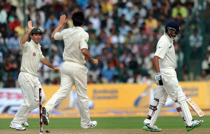 Australian cricketer captain Ricky Ponting (L) congratulates teammate Mitchell Johnson (C) for taking the wicket of Indian Cricketer Rahul Dravid (R) during the second day of the second Test between India and Australia at M.Chinnaswamy stadium in Bangalore. (AFP PHOTO)