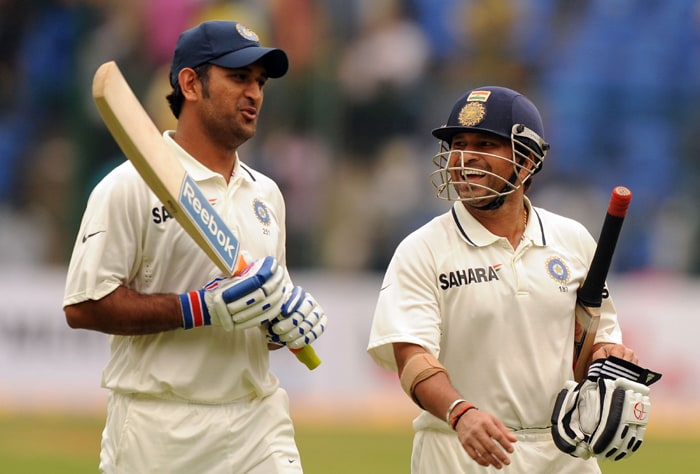Indian cricketer Sachin Tendulkar enjoys a moment with captain Mahendra Singh Dhoni as they walks back to the dressing room after the day's play, after the third day of the second Test between India and Australia at M. Chinnaswamy Stadium in Bangalore. (AFP Photo)