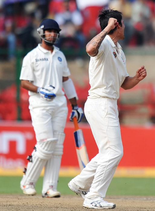 Australian cricketer Mitchell Johnson celebrates the wicket of Indian cricketer Cheteshwar Pujara (L) during the third day of the second Test between India and Australia at M. Chinnaswamy Stadium in Bangalore. (AFP Photo)