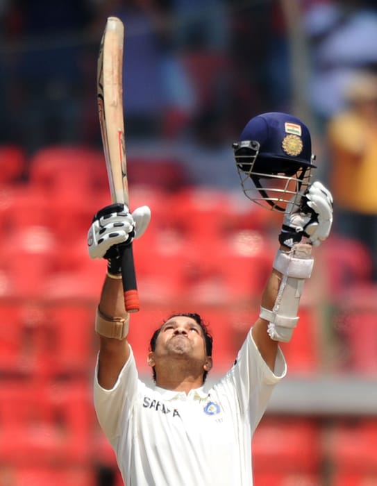 Indian cricketer Sachin Tendulkar celebrate his century during the third day of the second Test between India and Australia at M. Chinnaswamy Stadium in Bangalore. (AFP Photo)