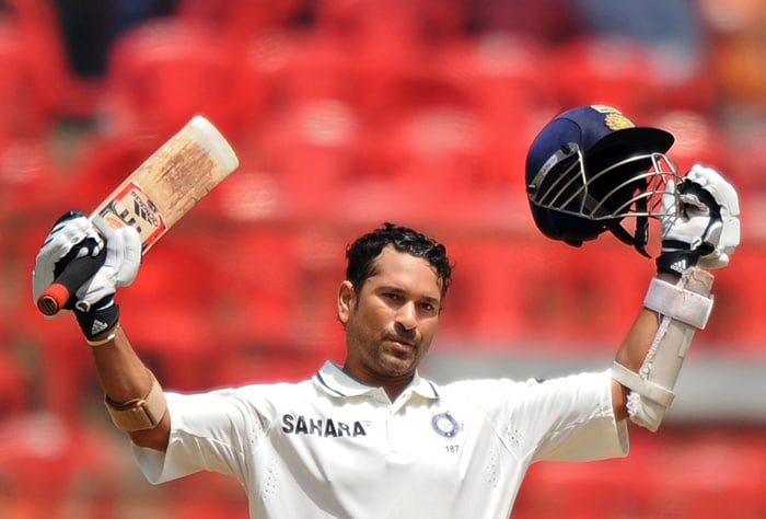 Indian cricketer Sachin Tendulkar celebrates his century during the third day of the second Test between India and Australia at M. Chinnaswamy Stadium in Bangalore. (AFP Photo)