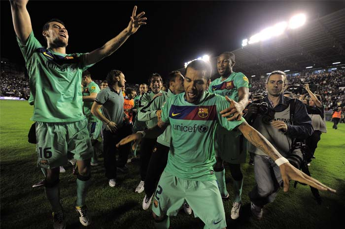 Barcelona's Brazilian defender Dani Alves (C) and midfielder Sergio Busquets (L) celebrate after the team was crowned Spanish champions for the third successive season with a 1-1 draw at Levante, clinching a 21st domestic title with two games to spare. (AFP PHOTO)